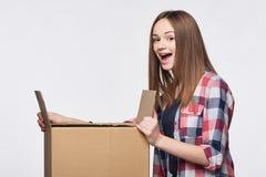 Vista lateral uma menina que abre uma caixa Imagens de Stock