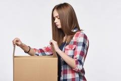 Vista lateral uma menina que abre uma caixa Imagens de Stock Royalty Free