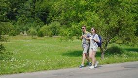 Vista lateral: un par turístico joven camina a lo largo del camino a las montañas hermosas cubiertas con la manera activa del bos almacen de video