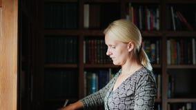 Vista lateral: Una mujer quita el polvo en los estantes con los libros, cepillando el polvo con un cepillo Limpieza de la casa almacen de video