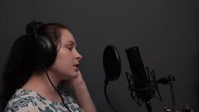 Vista laterale alta vicina della ragazza di canto in cuffie in studio di registrazione Addestramento vocale Canto romantico stock footage