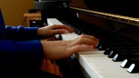 Vista laterale alta vicina di giovani mani e delle dita che giocano una canzone sulle chiavi di un piano nero brillante dritto stock footage