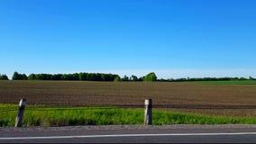 Vista laterale che guida dal campo rurale nel giorno punto di vista POV del driver che guida dopo i campi scenici della campagna archivi video