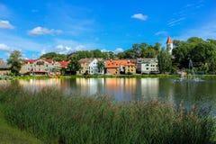 Vista laterale con mio luogo natio Talsi Camere che riflettono nel lago fotografie stock