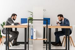 vista laterale degli uomini d'affari che lavorano e che bevono caffè immagini stock libere da diritti
