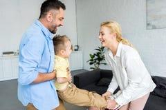 vista laterale dei bambini felici con il piccolo figlio adorabile divertendosi togetehr fotografie stock libere da diritti