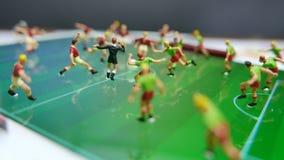 Vista laterale dei calciatori miniatura di calcio delle figurine dei giocattoli su un cuscinetto del computer