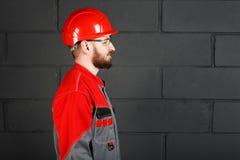 Vista laterale dei camici d'uso del lavoratore e casco e protecti rossi Fotografia Stock Libera da Diritti