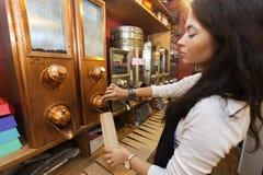 Vista laterale dei chicchi di caffè d'erogazione del commesso nel sacco di carta al deposito Fotografie Stock