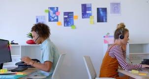 Vista laterale dei colleghi caucasici di affari che lavorano al loro computer portatile e che per mezzo di audio cuffia avricolar archivi video