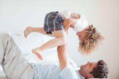 Vista laterale del bambino di sollevamento sorridente del padre Immagine Stock Libera da Diritti