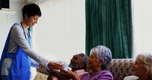 Vista laterale del caffè servente di medico femminile caucasico alla gente senior nella casa di cura 4k video d archivio