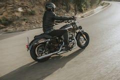 Vista laterale del cavaliere classico della motocicletta che guida un motociclo classico americano immagine stock libera da diritti