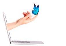 Vista laterale del computer portatile con la farfalla a disposizione Fotografie Stock
