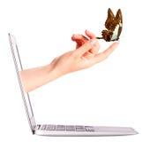 Vista laterale del computer portatile con la farfalla a disposizione Fotografia Stock Libera da Diritti