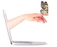 Vista laterale del computer portatile con la farfalla a disposizione Immagini Stock Libere da Diritti