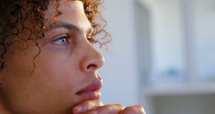 Vista laterale del grafico maschio caucasico con la mano su funzionamento del mento allo scrittorio in ufficio 4k stock footage