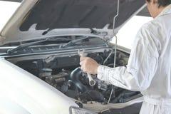 Vista laterale del meccanico automobilistico in uniforme di bianco con la chiave che diagnostica motore sotto il cappuccio dell'a fotografia stock libera da diritti