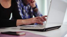 Vista laterale del primo piano delle mani di un gruppo creativo irriconoscibile di affari di tre genti che lavorano al computer p video d archivio