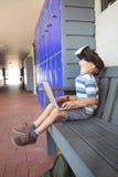 Vista laterale del ragazzo che usando i vetri di realtà virtuale e del computer portatile mentre sedendosi sul banco Fotografie Stock
