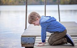 Vista laterale del ragazzo sul bacino che guarda nel lago Fotografia Stock