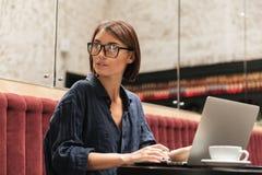 Vista laterale del responsabile femminile in occhiali che si siedono dalla tavola Immagini Stock Libere da Diritti