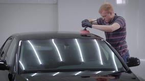 Vista laterale dell'uomo adulto che sta nel garage e che per mezzo della levigatrice sul tetto dell'automobile archivi video