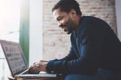 Vista laterale dell'uomo africano allegro che per mezzo del computer e sorridendo mentre sedendosi sul sofà Gente di affari dei g Immagine Stock