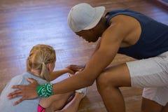 Vista laterale dell'uomo che assiste ballerino femminile nell'allungamento Immagini Stock