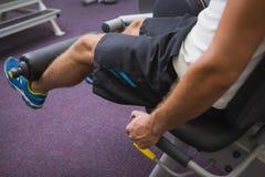 Vista laterale dell'uomo che fa allenamento della gamba alla palestra Immagini Stock