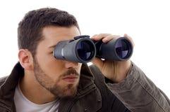 Vista laterale dell'uomo che osserva tramite il binocolo Immagini Stock