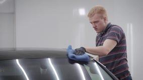 Vista laterale dell'uomo che pulisce il tetto dell'automobile con l'asciugamano blu in garage video d archivio