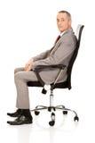 Vista laterale dell'uomo d'affari che si siede sulla poltrona Immagine Stock Libera da Diritti