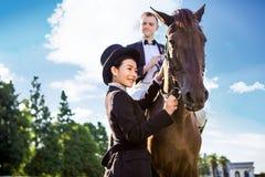 Vista laterale dell'uomo facente una pausa della donna felice che si siede sul cavallo contro il cielo Fotografia Stock Libera da Diritti