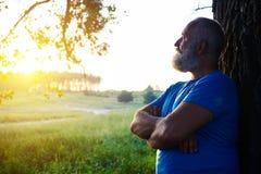 Vista laterale dell'uomo invecchiato bello vicino all'albero che esamina i soli fotografia stock
