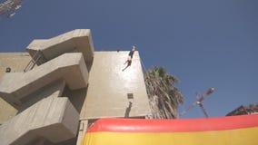 Vista laterale dell'uomo irriconoscibile che salta dall'alta costruzione e che cade in un trampolino gonfiabile al giorno soleggi video d archivio