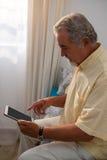 Vista laterale dell'uomo senior che per mezzo della compressa digitale mentre sedendosi sul letto immagine stock