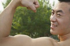 Vista laterale dell'uomo sorridente muscolare che ostenta e che flette il suo bicipite Fotografia Stock Libera da Diritti