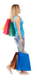 Vista laterale della donna andante con i sacchetti della spesa Fotografie Stock
