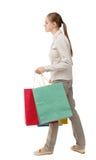 Vista laterale della donna andante con i sacchetti della spesa Immagini Stock Libere da Diritti
