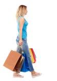 Vista laterale della donna andante con i sacchetti della spesa Fotografie Stock Libere da Diritti