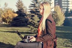Vista laterale della donna bionda felice in occhiali che si siedono sul banco in parco con il computer portatile Fotografia Stock Libera da Diritti