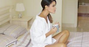 Vista laterale della donna calma che gode del caffè a letto stock footage