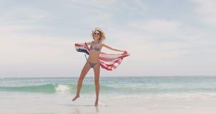 Vista laterale della donna caucasica con funzionamento d'ondeggiamento della bandiera americana sulla spiaggia 4k stock footage