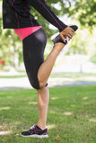 Vista laterale della donna che allunga la sua gamba durante l'esercizio al parco Immagini Stock Libere da Diritti