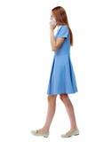 Vista laterale della donna che cammina con un telefono cellulare Fotografia Stock