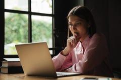 Vista laterale della donna concentrata che si siede dalla tavola in caffè Immagine Stock