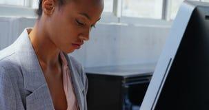 Vista laterale della donna di affari afroamericana che lavora al computer allo scrittorio in un ufficio moderno 4k archivi video