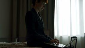 Vista laterale della donna di affari caucasica dell'mezzo adulto che lavora al computer portatile in un hotel moderno 4k archivi video