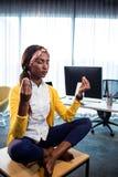 Vista laterale della donna di affari che fa yoga Fotografia Stock
